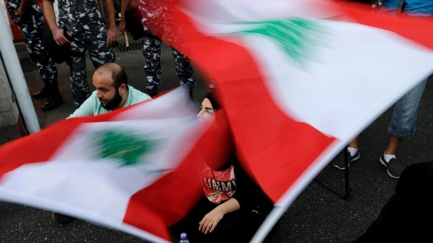 Lebanese activists wave national flags and shout slogans outside the interior ministry during a sit-in demanding the release of two protesters  arrested by plainclothes security agents at gunpoint in Beirut, Lebanon, Thursday, Sept. 3, 2015. (AP Photo/Hassan Ammar)