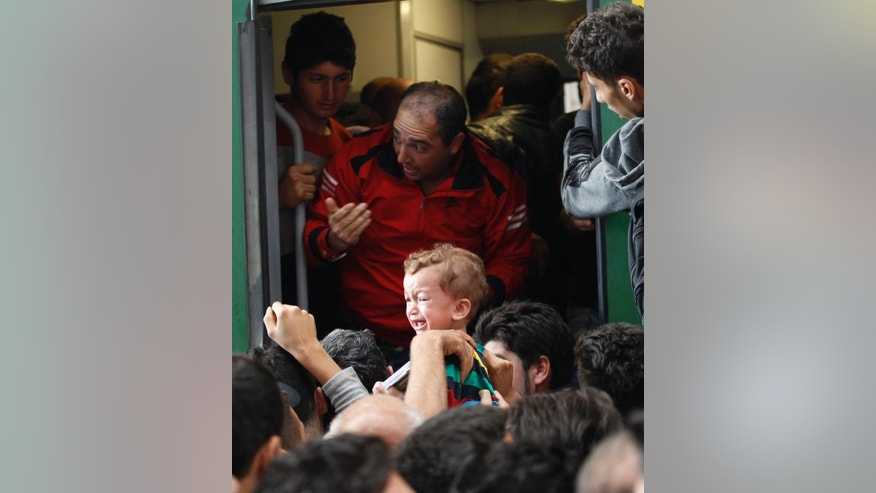 A young child cries as hundreds of migrants try to board a train at the Keleti Railway Station in Budapest, Hungary, Thursday, Sept. 3, 2015. Over 150,000 migrants have reached Hungary this year, most coming through the southern border with Serbia. Many apply for asylum but quickly try to leave for richer EU countries. (AP Photo/Petr David Josek)