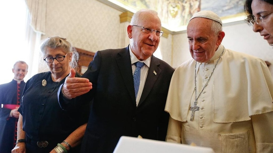 Pope Francis and Israel's President Reuven Rivlin exchange gifts during a private audience in the Pontiff's private library at the Vatican Thursday, Sept. 3, 2015. (Tony Gentile/Reuter via AP Pool)