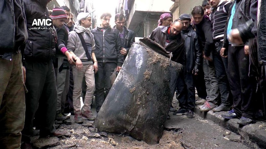 FILE - In this Sunday, Jan. 19, 2014 file photo, provided by Aleppo Media Center (AMC), an anti-Bashar Assad activist group, which has been authenticated based on its contents and other AP reporting, Syrian citizens inspect an unexploded barrel of explosives which was dropped from a Syrian forces helicopter, on a street in Aleppo, Syria. Barrel bombs, suicide bombs, beheadings and starvation _ to name just a few horrors. Most of the refugees are driven by an overriding need to escape what has essentially become a hell on earth in Syria, caught between Syrian President Bashar Assad's ruthless war machine and the Islamic State group's brutality.  (AP Photo/Aleppo Media Center, AMC, File)