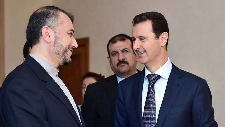 "In this photo released on the official Facebook page of the Syrian Presidency, Syrian President Bashar Assad, right, speaks with Iran's Deputy Foreign Minister Hossein Amir Abdollahian, left, in Damascus, Syria, Thursday, Sept. 3, 2015. Abdollahian says Syrian President Bashar Assad has a ""pivotal and central"" role to play in the war on terrorism and is an important part of any solution for the war-torn country. (Syrian Presidency via Facebook)"
