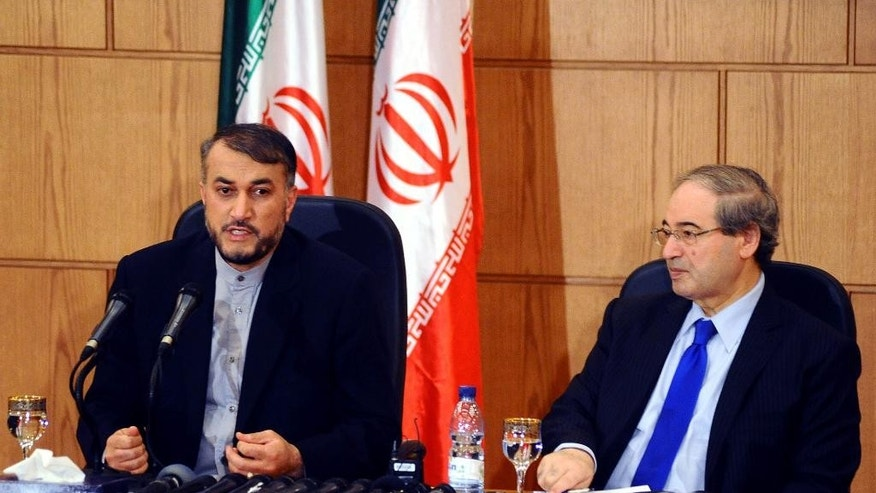 "In this photo released by the Syrian official news agency SANA, Iran's Deputy Foreign Minister Hossein Amir Abdollahian, left, sits next to his Syrian counterpart Faisal Mekdad, right, as he speaks during a joint press conference, in Damascus, Syria, Thursday, Sept. 3, 2015. Abdollahian says Syrian President Bashar Assad has a ""pivotal and central"" role to play in the war on terrorism and is an important part of any solution for the war-torn country. (SANA via AP)"