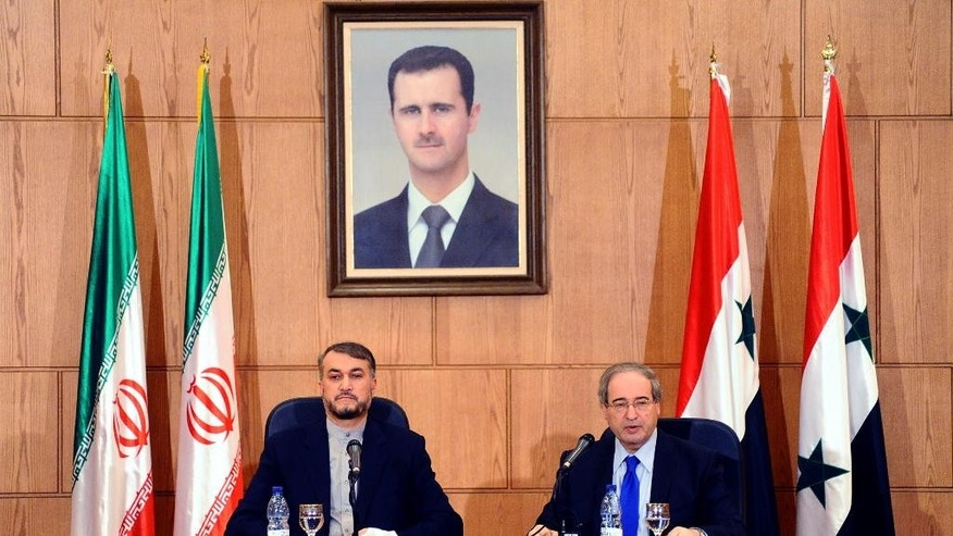 "In this photo released by the Syrian official news agency SANA, Iran's Deputy Foreign Minister Hossein Amir Abdollahian, left, sits next to his Syrian counterpart Faisal Mekdad, right, during a joint press conference, in Damascus, Syria, Thursday, Sept. 3, 2015. Abdollahian says Syrian President Bashar Assad has a ""pivotal and central"" role to play in the war on terrorism and is an important part of any solution for the war-torn country. (SANA via AP)"