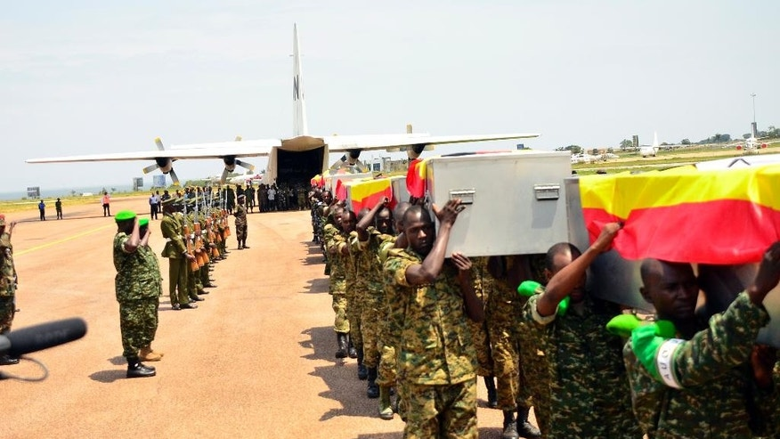 Ugandan soldiers carry the caskets of the Ugandan soldiers killed in Somalia, on arrival at Entebbe, Uganda, Thursday, Sept. 3, 2015. A Ugandan military spokesman says 12 Ugandan soldiers were killed in an attack Tuesday by Islamic extremists on an African Union base in Somalia. Lt. Col. Paddy Ankunda said Thursday that all soldiers were accounted for and that none was captured. He said 10 of the bodies will be flown back home Thursday. (AP Photo)