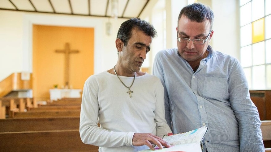 Iranian asylum-seekers Aref Movasaq Rodsari, left, and Vesam Heydari stand in the Trinity Church in Berlin, Germany, Aug. 13, 2015. Hundreds of mostly Iranian and Afghan asylum seekers who have converted to Christianity at the evangelical Trinity Church in the leafy Berlin neighborhood. Most say true belief prompted their embrace of Christianity, but there's no overlooking the fact that the decision will also greatly boost their chances of winning asylum by allowing them to claim they would face persecution if sent home. (AP Photo/Gero Breloer)