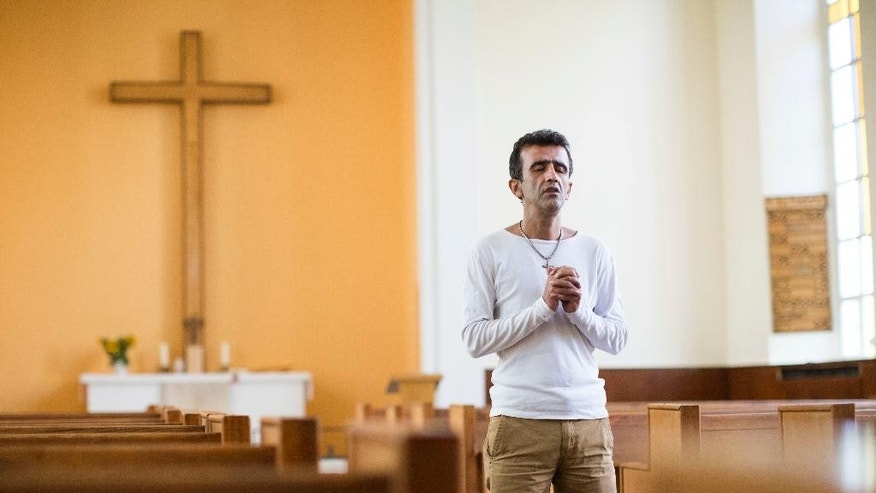 Iranian asylum-seeker Aref Movasaq Rodsari stands in the Trinity Church in Berlin, Germany, Aug. 13, 2015. He is one of hundreds of mostly Iranian and Afghan asylum seekers who have converted to Christianity at the evangelical Trinity Church in the leafy Berlin neighborhood. Most say true belief prompted their embrace of Christianity, but there's no overlooking the fact that the decision will also greatly boost their chances of winning asylum by allowing them to claim they would face persecution if sent home. (AP Photo/Gero Breloer)