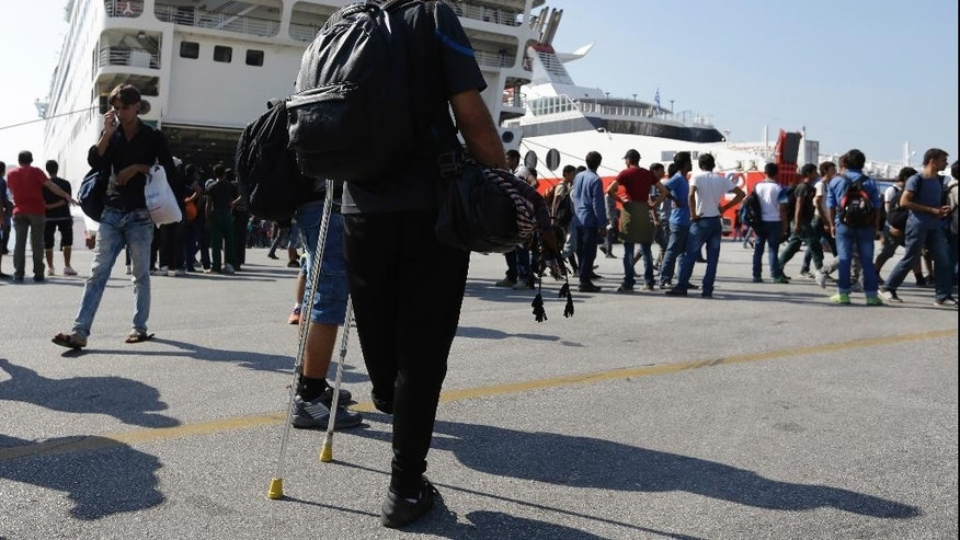 Syrian refugee, Mohammad, from the town of Dra, who lost his left leg during bombings in Damascus last year, waits at the Athens port of Piraeus on Friday, Sept. 4, 2015, after his arrival from the northeastern Greek island of Lesbos. About 2,500 people arrived on the ferry Eleftherios Venizelos. The Greek Government does not see an end to the flood of refugees and migrants anytime soon with the vast majority of migrants reaching five eastern Greek islands, with Lesbos seeing 50 percent of the arrivals. (AP Photo/Thanassis Stavrakis)