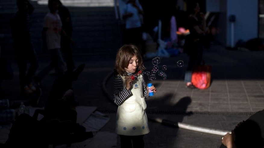 A girl blows soap bubbles at the Keleti train station in Budapest, Serbia, Friday, Sept. 4, 2015. Hundreds of migrants frustrated at being stuck at two train stations in Hungary set off on foot for Austria on Friday, one group forming a line nearly a half-mile long as they streamed out of Budapest, the other breaking out of a train near a migrant reception center and then running toward the West after overwhelming police. (AP Photo/Marko Drobnjakovic)