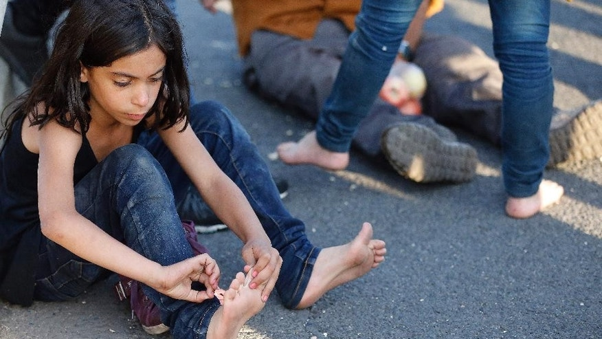 A young girl treats her feet  during their walk out of Budapest, Hungary, Friday, Sept. 4, 2015. Over 150,000 people seeking to enter Europe have reached Hungary this year, most coming through the southern border with Serbia, and many apply for asylum but quickly try to leave for richer EU countries. (AP Photo/Frank Augstein)