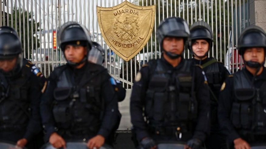 Guatemalan police officers stand guard at the Matamoros military barracks' presidential guard entrance, as they wait for the arrival of former President Otto Perez Molina, in Guatemala City, Thursday, Sept 3, 2015. Perez Molina was taken into custody and ordered to spend the night at the military barracks before a court hearing into corruption allegations against him reconvenes. He was taken from the court in an SUV and escorted by a dozen police vehicles. (AP Photo/Moises Castillo)
