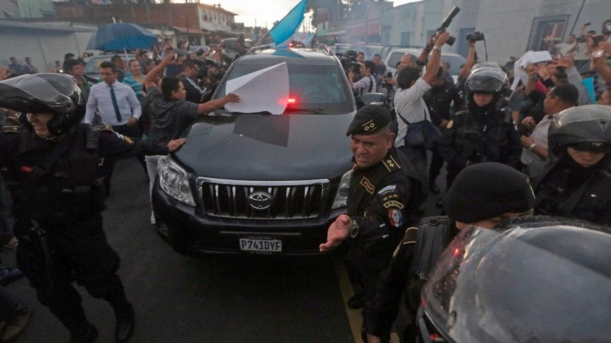 Guatemalan police officers try to clear a path for a vehicle carrying former President Otto Perez Molina, as he is transported to the Matamoros military barracks, in Guatemala City, Thursday, Sept 3, 2015. Perez Molina will spend the night in custody before a court hearing into corruption allegations against him reconvenes. He was taken from the court in an SUV and escorted by a dozen police vehicles. (AP Photo/Esteban Felix)