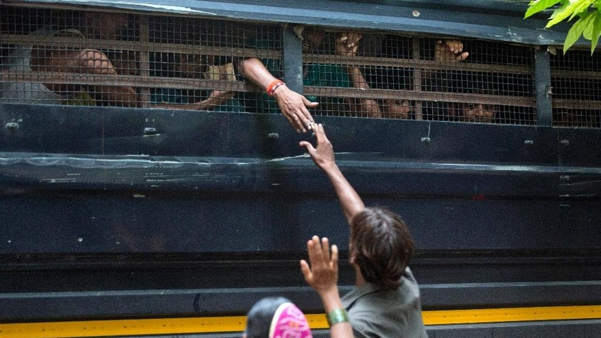 In this Friday, Aug. 28, 2015 photo, a relative slips money to a prisoner, as a jail van carrying inmates drives out of the district court premise gate towards Naini Central Jail after a hearing of undertrials in Allahabad, in the northern Indian state of Uttar Pradesh. There are tens of thousands of prisoners in Uttar Pradesh, where at least 70 percent of the state's 84,228 inmates have languished in jail because they cannot afford to pay bail while their cases take years or even decades to wend through India's notoriously slow and backlogged judicial system, according to the state's Jail Ministry. (AP Photo/Rajesh Kumar Singh)
