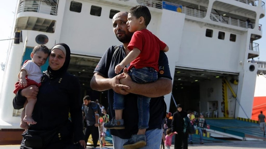 A family arrives from the northeastern Greek island of Lesbos to the Athens port of Piraeus, Friday, Sept. 4, 2015. About 2,500 people arrived on the ferry Eleftherios Venizelos. The Greek Government does not see an end to the flood of refugees and migrants anytime soon with the vast majority of migrants reaching five eastern Greek islands, with Lesbos seeing 50 percent of the arrivals. (AP Photo/Thanassis Stavrakis)