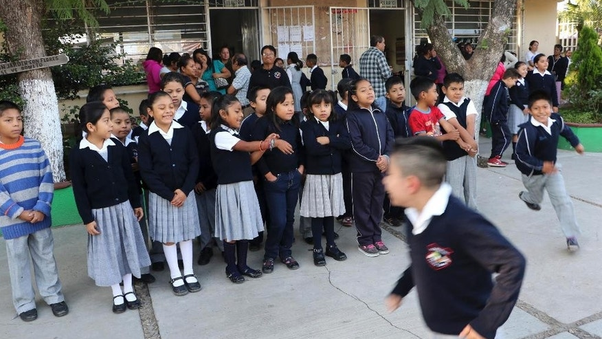 In this Aug. 24, 2015 photo, children line up during the first day of school in Oaxaca, Mexico. The scene is anything but normal in Oaxaca, a Mexican state where teachers' strikes and protests cost the average student 50 days out of the 200-day academic calendar last year, according to federal education officials. (AP Photo/Luis Alberto Cruz Hernandez)