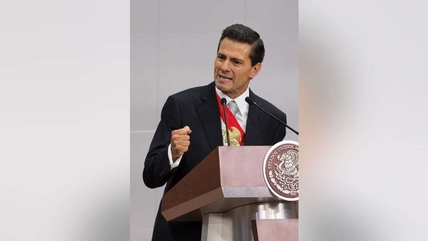 "Mexico's President Enrique Pena Nieto gestures with a closed fist as he wraps up his third State of the Nation address, inside the National Palace in Mexico City, Wednesday, Sept. 2, 2015. Pena Nieto began the speech by talking about the disappearance of 43 students in 2014, and the escape of drug lord Joaquin ""El Chapo"" Guzman. He said those events ""bother and disturb us as a society."" (AP Photo/Rebecca Blackwell)"