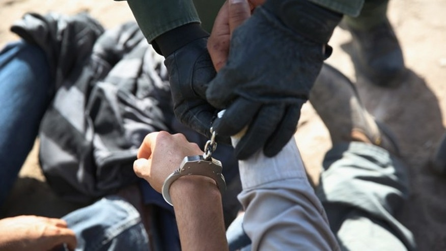 A U.S. Border Patrol agent handcuffs an undocumented immigrant near the U.S.-Mexico border on April 11, 2013 near Mission, Texas. (Photo by John Moore/Getty Images)