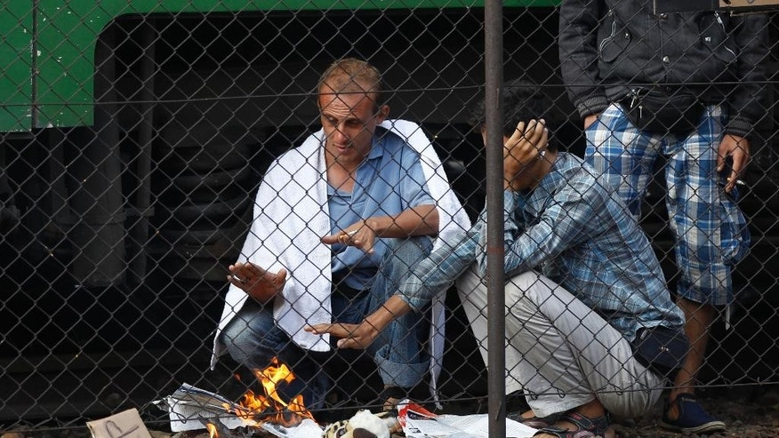 Men burn papers to warm themselves outside a train that was stopped in Bicske, Hungary, Friday, Sept. 4, 2015. Over 150,000 migrants have reached Hungary this year, most coming through the southern border with Serbia. Many apply for asylum but quickly try to leave for richer EU countries. (AP Photo/Petr David Josek)