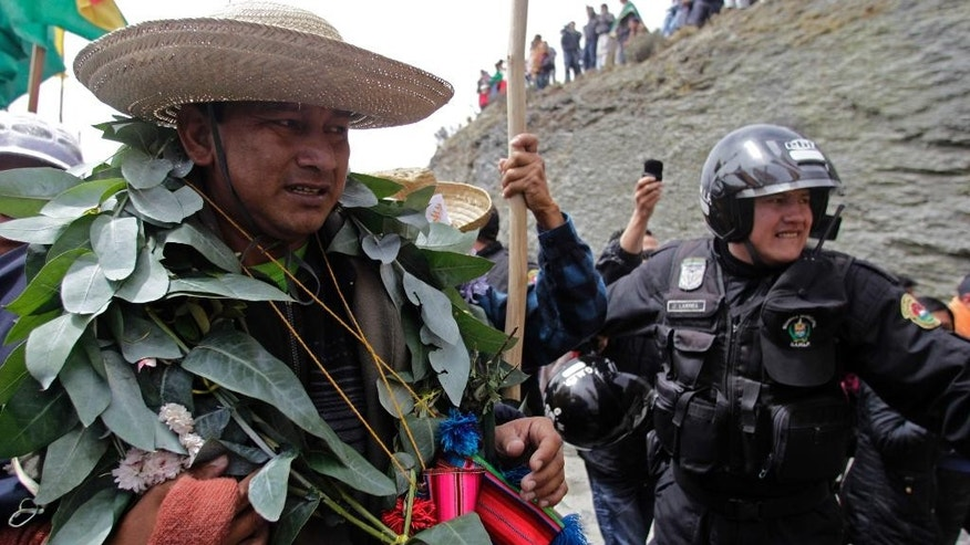 FILE - In this Oct. 18, 2011 file photo, indigenous leader Adolfo Chavez, left, is escorted by police officers, as he arrives in La Cumbre, Bolivia. The leader who has been openly critical of President Evo Morales' push to drill for oil and develop mining on traditional native lands in the eastern lowlands, was arrested by Bolivian authorities in a corruption probe.  Chavez says he's innocent and the object of political persecution. (AP Photo/Dolores Ochoa, File)
