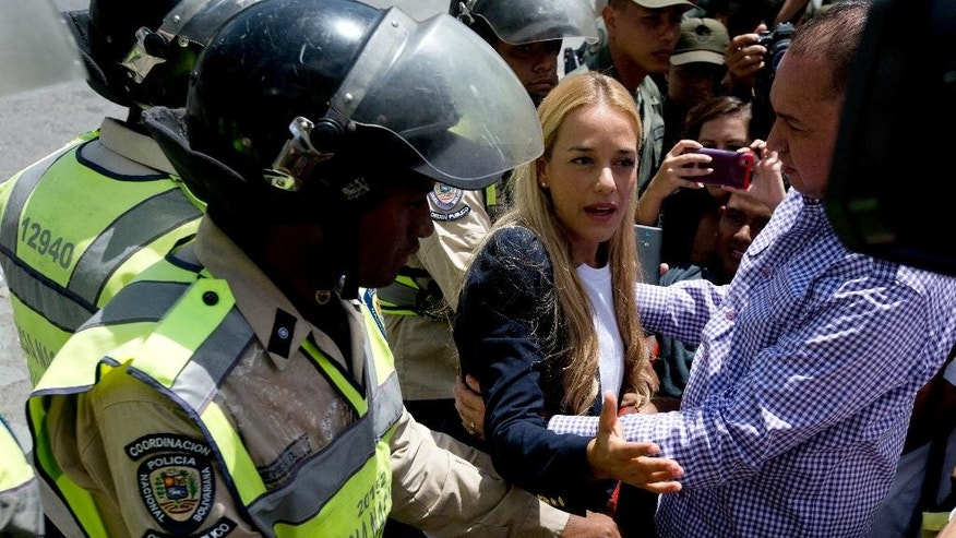 Lilian Tintori, center, wife of jailed opposition leader Leopoldo Lopez, speaks to the press as opposition lawmaker Richard Blanco helps project her from the crowd of press and supporters, outside court where Bolivarian National Police block her from entering where her husband will appear before a judge in Caracas, Venezuela, Friday, Sept. 4, 2015. The 19-month trial of the Venezuelan opposition leader is coming to a close on Friday as the imprisoned politician prepares to give his final remarks in a closed courtroom. Lopez is charged with inciting violence in his role as leader of a bloody protest movement in 2014, and could face more than 10 years in prison. (AP Photo/Fernando Llano)