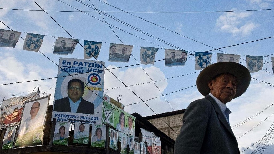 A man walks on a street backdropped by a wall of campaign posters promoting presidential and mayoral candidates, in Patzun, Guatemala, Friday, Sept 4, 2015. A wave of political turmoil that toppled Guatemala's president has overshadowed Sunday's vote to elect a new leader. Tens of thousands who demonstrated for the ouster of President Otto Molina Perez got part of their wishes when the president resigned to face possible corruption charges. But a second demand wasn't met: the postponement of the election that many said offered little alternative to the old guard. (AP Photo/Esteban Felix)