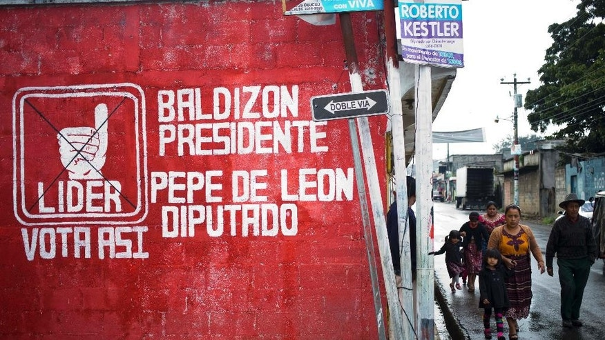 Pedestrians walk near a wall painted with a message promoting the presidential candidate and representative of the Democratic Freedom Revival Party, in Patzun, Guatemala, Friday, Sept 4, 2015. After Manuel Baldizon's campaign blew through the legal ceiling on electoral spending, he continued pouring money into his campaign, ignoring court orders to stop. Baldizon's most competitive rivals are a comedian with no political experience, a former first lady and the daughter of an ex-dictator accused of genocide. If none of the 14 candidates reaches 50 percent, a runoff will be held Oct. 25. (AP Photo/Esteban Felix)