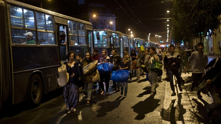 People walk before boarding buses provided by Hungarian authorities for migrants and refugees at Keleti train station in Budapest, Hungary, Saturday, Sept. 5, 2015. Hundreds of migrants boarded buses provided by Hungary's government as Austria in the early-morning hours said it and Germany would let them in. Austrian Chancellor Werner Faymann announced the decision early Saturday after speaking with Angela Merkel, his German counterpart - not long after Hungary's surprise nighttime move to provide buses for the weary travelers from Syria, Iraq and Afghanistan. (AP Photo/Marko Drobnjakovic)