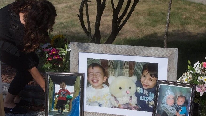 CORRECTS SPELLING OF GHALIB ON SECOND REFERENCE- Family friend Nissy Koye, left, places flowers beside photographs of late brothers Alan and Ghalib Kurdi and their mother displayed outside the home of their aunt Tima Kurdi, in Coquitlam, British Columbia, Friday, Sept. 4, 2015. The body of 3-year-old Syrian Alan Kurdi was found on a Turkish beach after the small rubber boat he, his 5-year old brother Ghalib and their mother were in capsized during a desperate voyage from Turkey to Greece. Abdullah Kurdi buried his wife and their two sons in their hometown of Kobani on Friday. (Darryl Dyck/The Canadian Press via AP) MANDATORY CREDIT