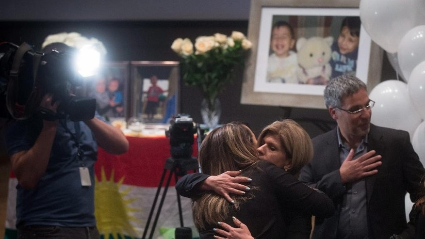 Tima Kurdi, center right, aunt of late brothers Alan and Ghalib Kurdi, is embraced by a woman during a memorial service for the boys and their mother, as her husband Rocco Logozzo, right, stands by in Vancouver, British Columbia, Canada on Saturday, Sept. 5, 2015. The body of 3-year-old Alan was found on a Turkish beach after the small rubber boat he, his 5-year-old brother, Ghalib and their mother, Rehanna, were in capsized during a voyage from Turkey to Greece. (Darryl Dyck/The Canadian Press via AP) MANDATORY CREDIT