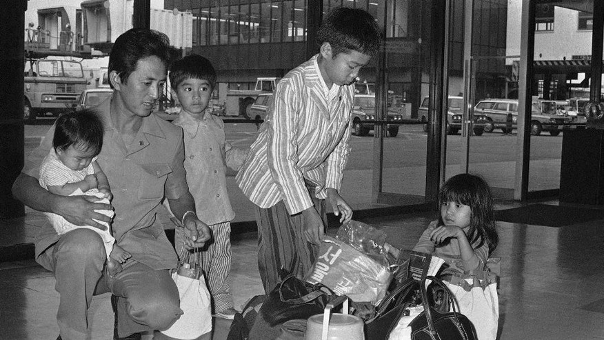 FILE - In this Aug. 26, 1975 file photo, a family fleeing South Vietnam wait for a Canada-bound plane at the Tokyo International Airport. From left are Nguyen Tan Canh, holding his four-month-old boy Tan Linh Buu; Khanh Linh; Hoa Khanh and Thi Ngoc. They fled Vietnam on April 26 aboard a refugee vessel and arrived in Korea on May 13 and decided to resettle in Canada. Canada has long prided itself for opening its doors wider than any nation to asylum seekers, but the number it welcomes has waned since the Conservative Prime Minister Stephen Harper took power almost 10 years ago. (AP Photo)