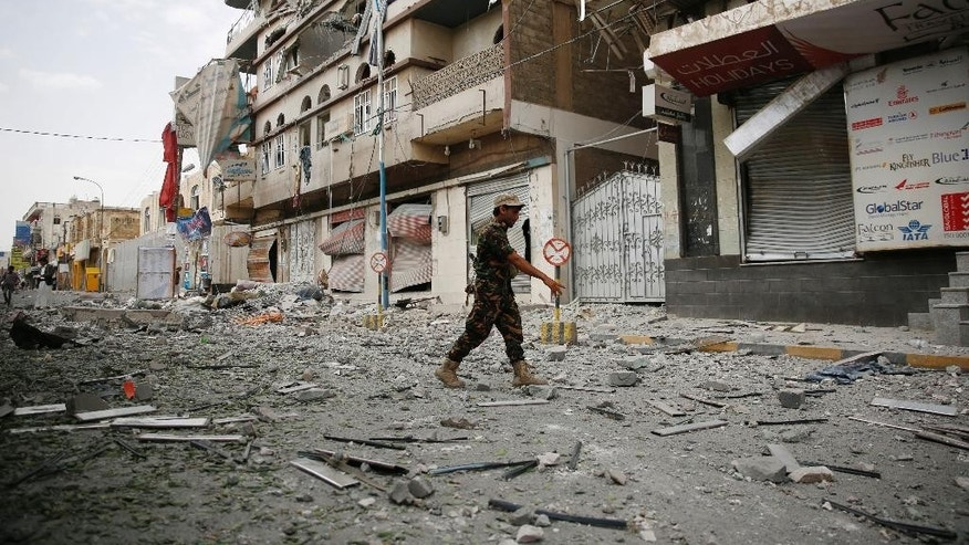 A soldier stands guard in front of the buildings destroyed by a Saudi-led airstrike in Sanaa, Yemen, Saturday, Sept. 5, 2015. (AP Photo/Hani Mohammed)