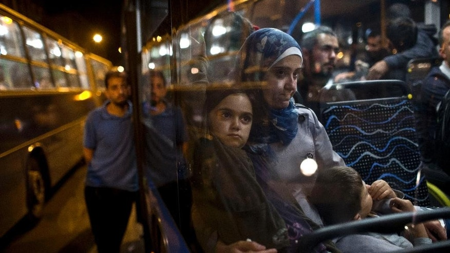 A woman and her children sit as they have boarded a bus provided by Hungarian authorities for migrants and refugees at Keleti train station in Budapest, Hungary, Saturday, Sept. 5, 2015. Hundreds of migrants boarded buses provided by Hungary's government as Austria in the early-morning hours said it and Germany would let them in. Austrian Chancellor Werner Faymann announced the decision early Saturday after speaking with Angela Merkel, his German counterpart - not long after Hungary's surprise nighttime move to provide buses for the weary travelers from Syria, Iraq and Afghanistan.  (AP Photo/Marko Drobnjakovic)
