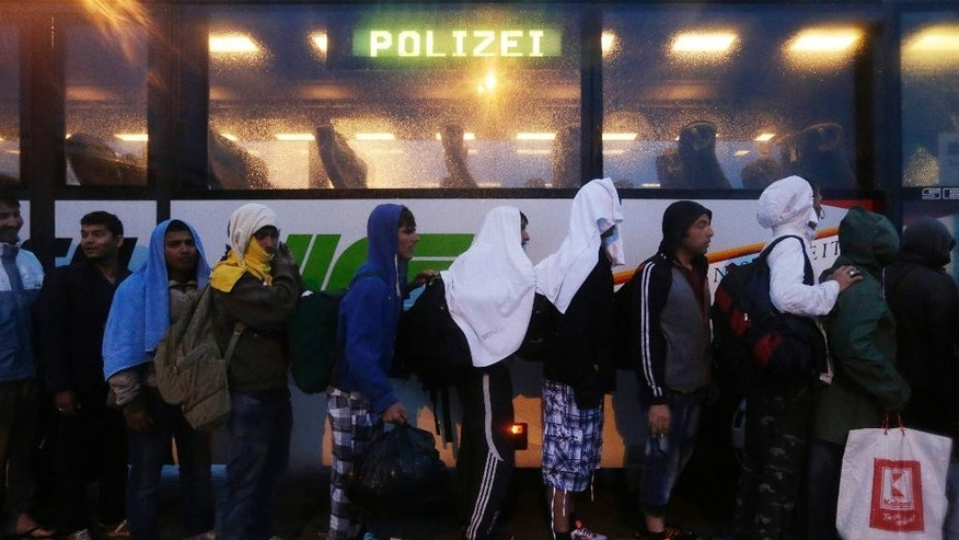 Migrants  line up in front of a police bus at the Hungarian-Austrian border in Nickelsdorf,  Austria, Saturday, Sept. 5, 2015, where they arrived from Budapest as Austria in the early-morning hours said it and Germany would let them in. (AP Photo/Petr David Josek)