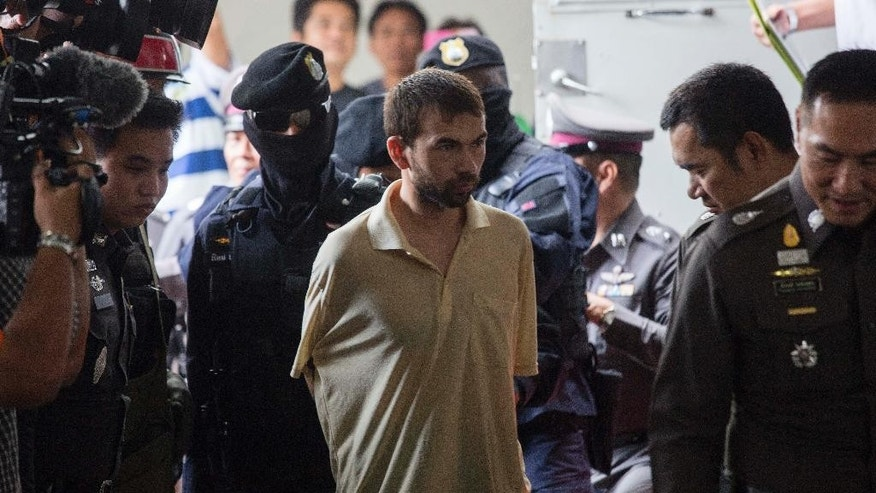 The suspect who was arrested at an apartment last week and found with evidence police said included bomb making equipment and stacks of fake passports arrives at court in the Min Buri district of Bangkok, Thailand, to extend his detention by police on Saturday, Sept. 5, 2015, after he was handed over from military custody Friday. The suspect's identity has not been confirmed. The Aug. 17 blast at the shrine popular among locals and tourists alike left 20 people dead and more than 120 injured in one of the most devastating acts of violence that the Thai capital had seen in decades. (AP Photo/Wason Wanichakorn)