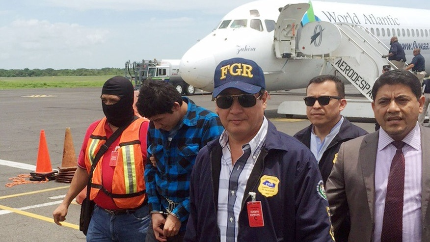 In this photo provided by U.S. Immigration and Customs Enforcement, Salvadoran Attorney General Luis Martinez, in blue cap, escorts Javier Arnoldo Ceron Gomez, second from left, across the tarmac at the airport in San Salvador, El Salvador, as Ceron is repatriated Friday, Sept. 4, 2015. Ceron, 21, a member of the notorious MS-13 gang, was wanted in connection with the March shooting death of Salvadoran prosecuting attorney Andres Ernesto Oliva Tejada. ICE flew him from Mesa, Ariz., to San Salvador and turned him over to authorities. (Immigration and Customs Enforcement via AP)