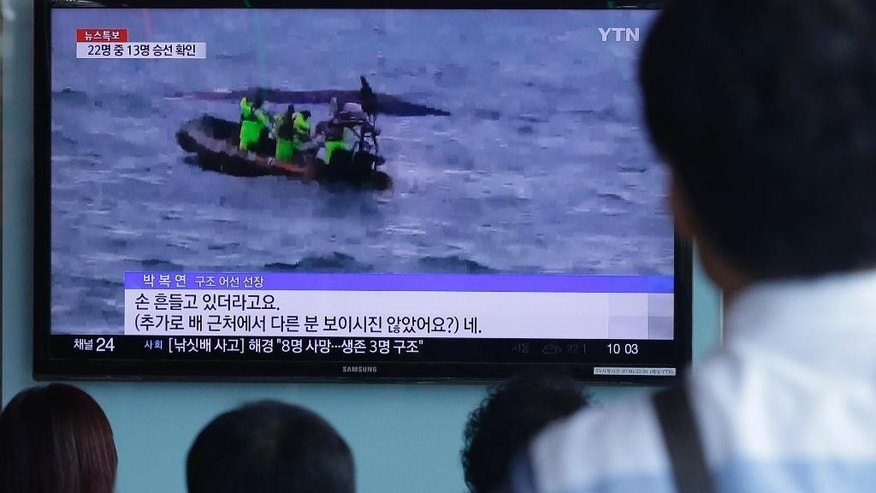 People watch a TV news program showing South Korean Coast Guard officers search for missing passengers after a fishing boat capsized in the water off north of the resort island of Jeju,  at Seoul Railway Station in Seoul, South Korea, Sunday, Sept. 6, 2015. (AP Photo/Ahn Young-joon)