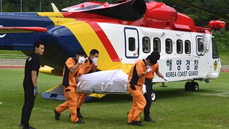 The victim's body who was onboard a capsized fishing boat in the water off north of the resort island of Jeju,  is carried by rescue workers upon its arrival in Haenam, South Korea, Sunday, Sept. 6, 2015. The 9.8-ton boat, Dolphin, lost communication with officials on Saturday evening and was found Sunday morning north of the resort island of Jeju. A witness told Yonhap news agency that the boat quickly capsized because of high waves. (Ryu Hyung-geun/Newsis via AP) KOREA OUT