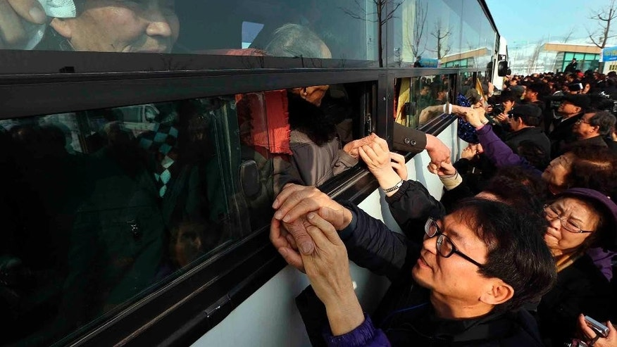 FILE - In this Feb. 25, 2014 file photo, South Koreans hold their North Korean relative's hands on a bus after the Separated Family Reunion Meeting at Diamond Mountain in North Korea. North and South Korea started talks at a border village Monday, Sept. 7, 2015,  on resuming the reunions of families separated by the Korean War in the early 1950s, Seoul officials said.  The highly emotional reunions have not happened since early last year. Most applicants are in their 70s or older and desperate to see their loved ones before they die.  (Lee Ji-eun/Yonhao via AP, File) KOREA OUT
