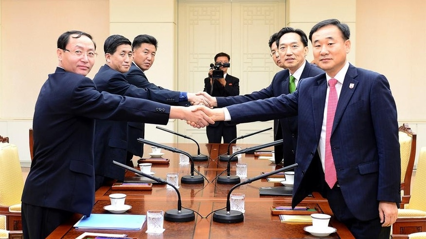 In this photo provided by South Korea's Unification Ministry, South Korea's chief delegate Lee Deok-haeng, second from right, shakes hands with North Korean counterpart Pak Yong Il, second from left, before the Inter-Korean Red Cross working level meeting at the border village of the Panmunjom in Paju, South Korea, Monday, Sept. 7, 2015. North and South Korea started talks at a border village Monday on resuming the reunions of families separated by the Korean War in the early 1950s, Seoul officials said. (The Unification Ministry via AP)