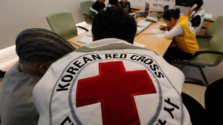 South Koreans who were separated from their families during the Korean War, talk with Red Cross members as they check application forms to reunite with their family members living in North Korea, at the Korea Red Cross headquarters in Seoul, South Korea, Monday, Sept. 7, 2015. North and South Korea started talks at a border village Monday on resuming the reunions of families separated by the Korean War in the early 1950s, Seoul officials said. (AP Photo/Lee Jin-man)