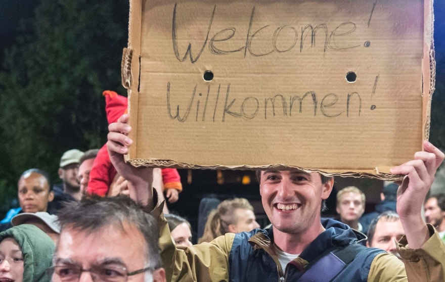 Sept. 5, 2015: A man holds a cardboard with a 'Welcome' slogan during the arrival of refugees at the train station in Saalfeld, central Germany