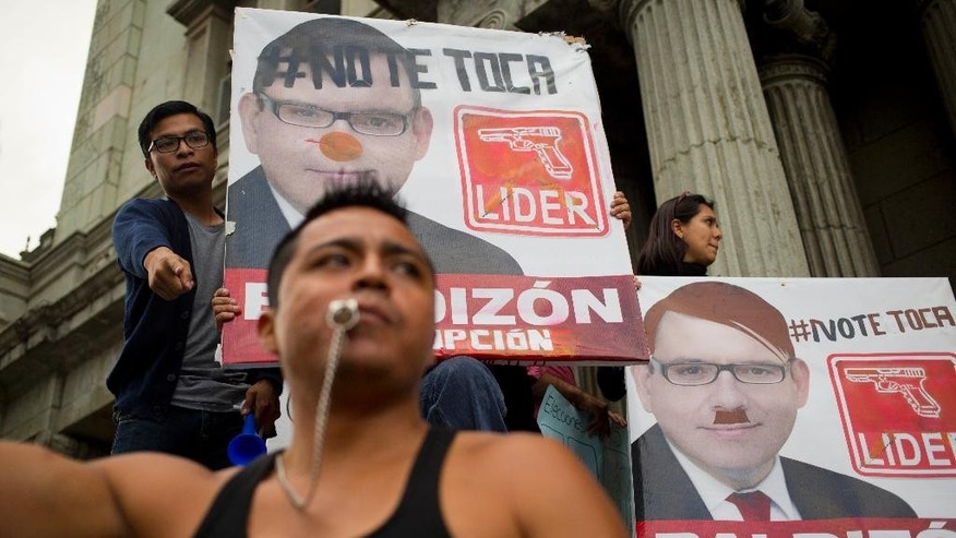 "Demonstrators hold defaced campaign posters of presidential hopeful Manuel Baldizon, of the Democratic Freedom Revival Party, as they demand election reform in Guatemala City, Saturday, Sept. 5, 2015, the day before general elections. Voters will go to the polls Sunday for normally scheduled general elections less than a week after Otto Perez Molina resigned as president. The signs read in Spanish: ""It's not your turn,"" top left, and ""Corrupt.""  (AP Photo/Moises Castillo)"