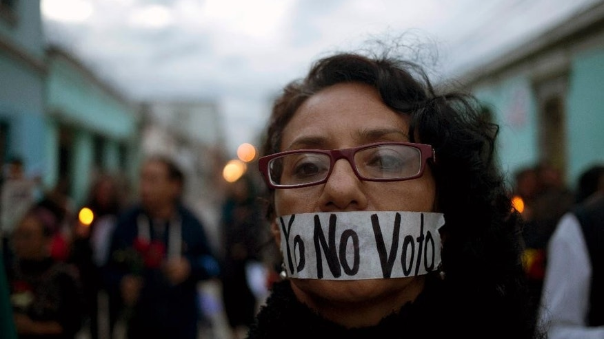 "A demonstrator covers her mouth with tape carrying the message Spanish: ""I'm not voting,"" during a protest demanding election reform in Guatemala City, Saturday, Sept. 5, 2015, the day before general elections. Voters will go to the polls Sunday for normally scheduled general elections less than a week after Otto Perez Molina resigned as president. (AP Photo/Moises Castillo)"