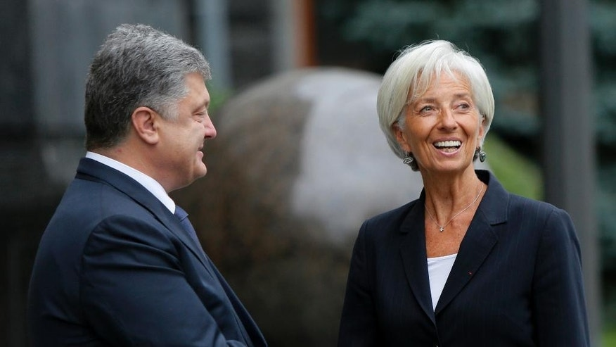 Ukrainian President Petro Poroshenko, left, and Managing Director of the International Monetary Fund Christine Lagarde shake hands during their meeting in Kiev, Ukraine, Sunday, Sept. 6, 2015. (AP Photo/Sergei Chuzavkov)