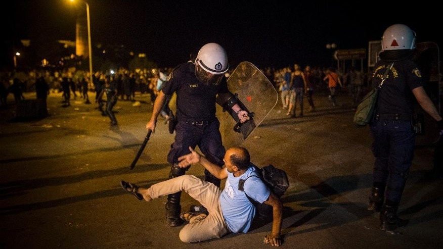 A migrant is confronted by a riot policeman during a protest in which hundreds of migrants and refugees demanded the authorities to let them go to Athens and continue their trip towards Northern Europe, at the port of Mytilene, on the northeastern Greek island of Lesbos, on Saturday, Sept. 5, 2015. (AP Photo/Santi Palacios)