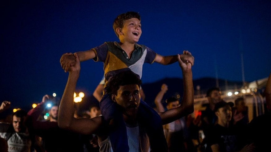 Refugees and migrants take part in a protest demanding the authorities to let them go to Athens and continue their trip towards Northern Europe, at the port of Mytilene, on the northeastern Greek island of Lesbos, on Saturday, Sept. 5, 2015. Earlier many of them confronted the police as they attempted to get onboard a ship bound to Athens' port of Piraeus. (AP Photo/Santi Palacios)