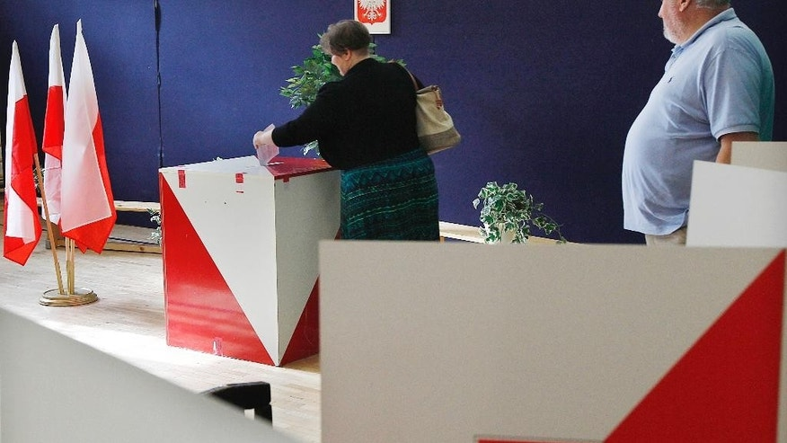 Polish voters arrive at a voting station to vote in a referendum in Warsaw, Poland, on Sunday Sept. 6, 2015. The referendum asks voters if they want the country to introduce a U.K.-style single-member constituency to the lower house of parliament, whether to end public funding for political parties and whether disputes between taxpayers and the authorities should be resolved in favor of the taxpayers. (AP Photo/Czarek Sokolowski)
