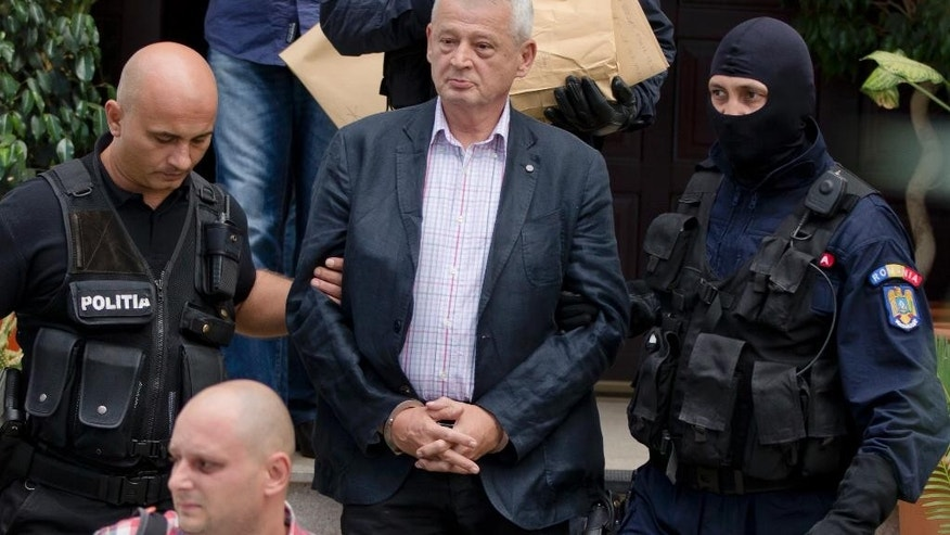 Police officers escort the handcuffed mayor of Bucharest Sorin Oprescu from his house in Ciolpani, Romania, Sunday, Sept. 6, 2015. Anti-corruption prosecutors in Romania detained the influential mayor of Bucharest early Sunday on suspicion that he took bribes of euro 25,000 (US$28,000) from firms working for the city hall. (AP Photo/Vadim Ghirda)