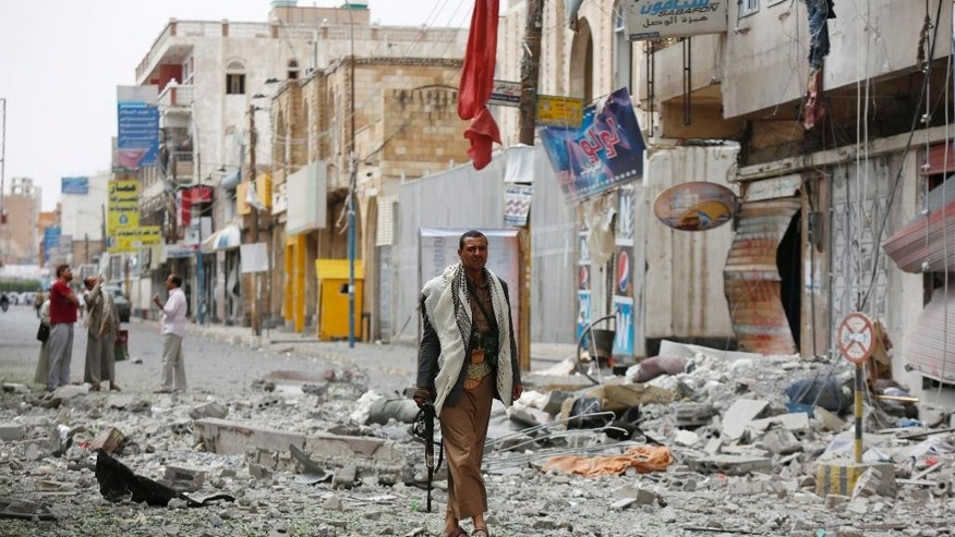 A Shiite fighter known as a Houthi stands guard in front of buildings destroyed by a Saudi-led airstrike in Sanaa, Yemen, Saturday, Sept. 5, 2015. (AP Photo/Hani Mohammed)