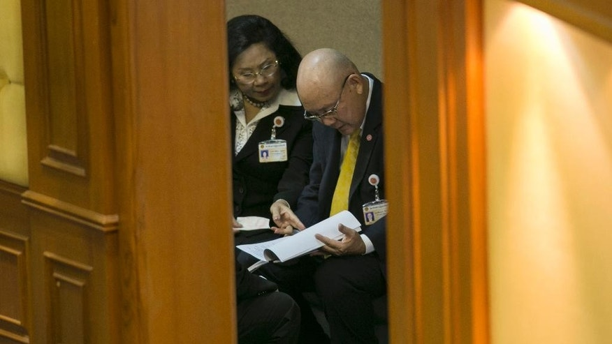 Thienchai Kiranan, right, president of Thailand's legislature, known as the National Reform Council, looks over notes before the start of the session before the body voted on the new draft constitution Sunday, Sept. 6, 2015, in Bangkok, Thailand. Thailand's military-backed legislature on Sunday rejected an unpopular draft of a new constitution, delaying a return to democracy following a coup last year. (AP Photo/Wason Wanichakorn)