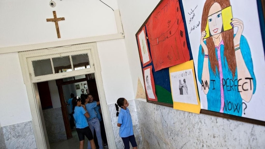 FILE - In this Tuesday, May 26, 2015 file photo, An Arab Israeli Christian school girl looks at a board with drawings at the Terra Santa School in the mixed Jewish-Arab city of Ramle, Israel. About 2,500 striking demonstrators gathered Sunday, Sept. 6, 2015, outside the prime minister's office in Jerusalem, police said, to protest against the slashing of funds for Christian schools. Christian school administrators accuse Israel of cutting their funding as a tactic to pressure them to join the Israeli public school system _ a move they say would interfere with the schools' Christian values and high academic achievements. (AP Photo/Oded Balilty, File)